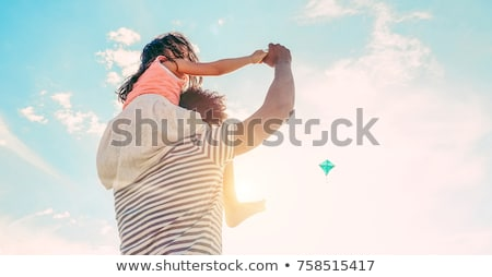 father and daughter having fun flying kite on beach holiday stock photo © monkey_business