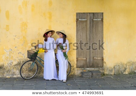 Attractive Vietnamese woman with yellow flowers Stock photo © smithore