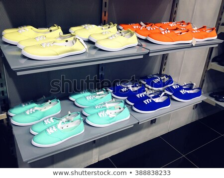 Collection of colorful casual gumshoes on shelves in fashion sto Stock photo © pzaxe