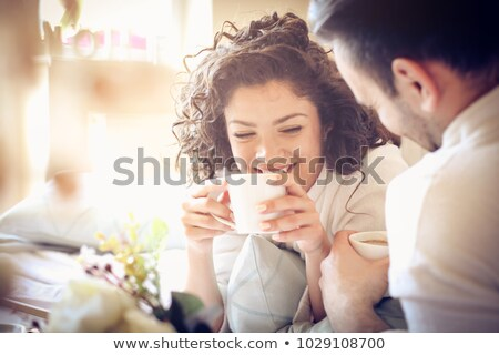 couple drinking coffee lying in the bed at home stock photo © dashapetrenko