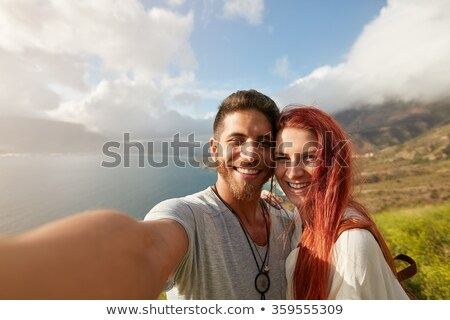 Happy man and woman taking self portrait with mountain scenery Stock photo © deandrobot