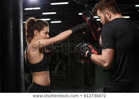concentrated young strong sports lady boxer with man trainer stock photo © deandrobot