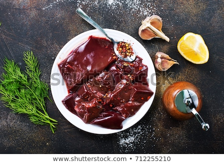 raw liver on slate board on wooden background top view stock photo © yelenayemchuk