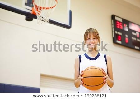 Smiling asian teen female holding basketball stock photo © palangsi