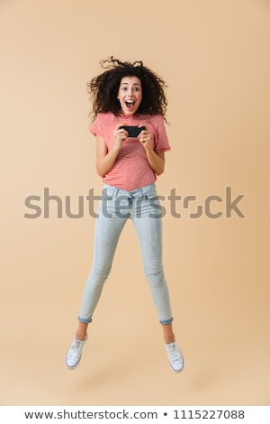 Portrait of an excited SMILING girl playing games Stock photo © deandrobot