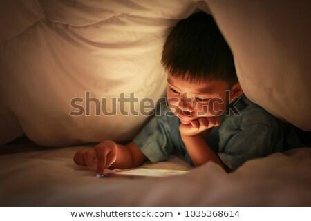 Kid using tablet with light reflex on face. Stock photo © vinnstock