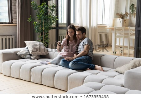 Stock photo: Happy lovely couple sitting on couch and making selfie