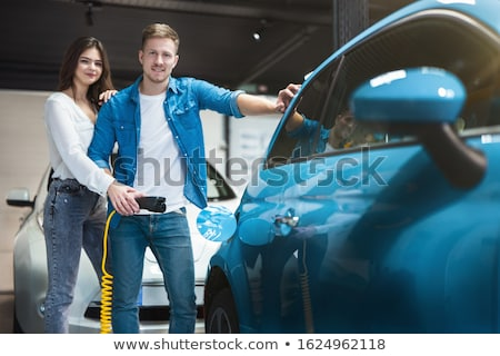 Stock photo: Couple standing by their electric car