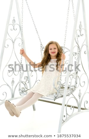 portrait of a charming blonde sitting on a swing stock photo © konradbak