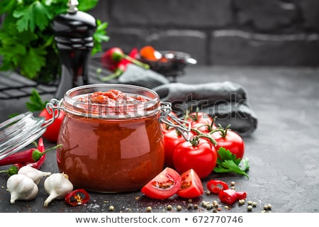 Glass of fresh organic tomato paste with fresh raw tomatoes basil and pepper in box on stone kitchen Stock photo © DenisMArt