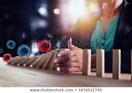 Businesswoman stops a chain fall like domino game. Concept of preventing crisis and failure in busin Stock photo © alphaspirit