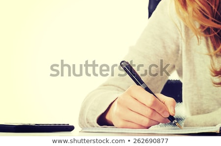 girl writing with pen at the table stock photo © Lopolo