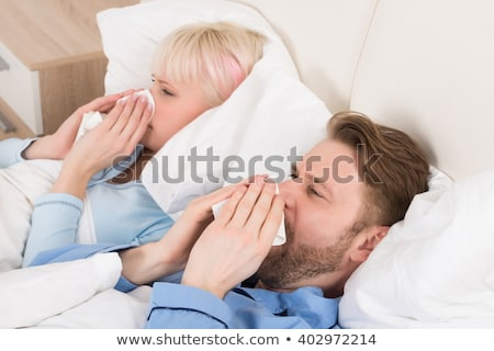 Photo stock: Sick Couple Lying On Bed Blowing Their Nose