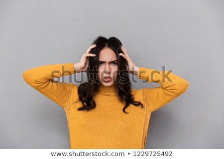 Image of frustrated woman 30s with long dark hair frowning and g Stock photo © deandrobot