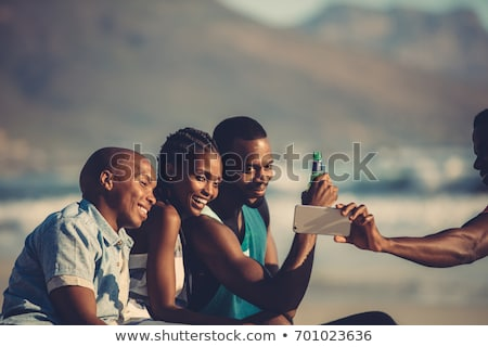woman picturing friends by smartphone at picnic Stock photo © dolgachov