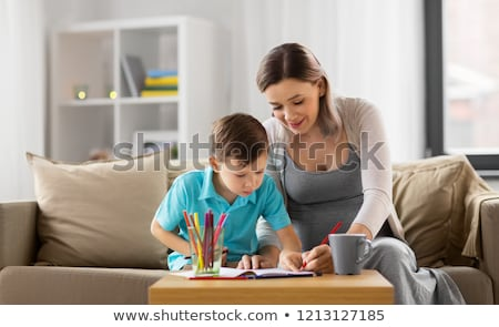 pregnant mother and son with workbook at home Stock photo © dolgachov
