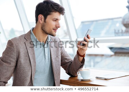 businessman chatting on mobile phone and reading newspaper stock photo © lichtmeister