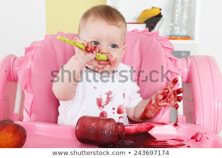 Naughty baby eating alone in the high chair Stock photo © Lopolo