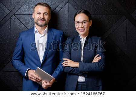 happy successful colleagues in formalwear standing in front of camera by wall stock photo © pressmaster