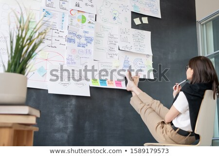 Young barefoot businesswoman sitting in front of blackboard and analyzing data Stock photo © pressmaster