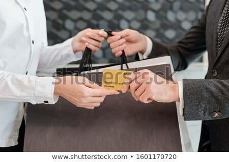 Hands of young man passing credit card to shop assistant while taking paperbags Stock photo © pressmaster