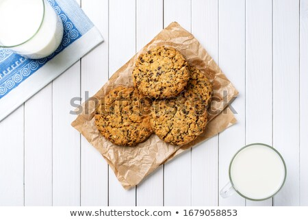 Cup of milk and stack of fresh baked oat cookies on rustic woode Stock photo © marylooo