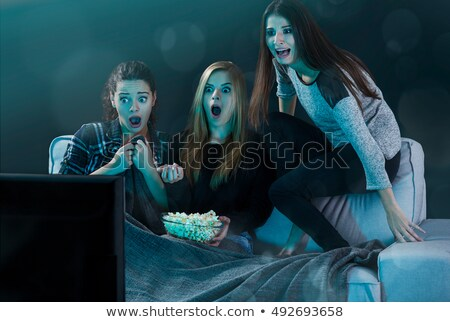 scared family with popcorn watching horror on tv Stock photo © dolgachov