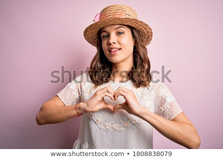 Image of young girl wearing hat smiling and showing heart shape Stock photo © deandrobot