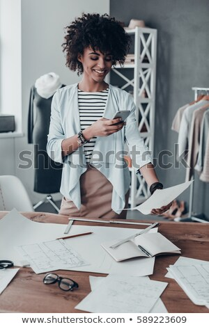 Photo of woman using mobile phone while standing at clothes rack Stock photo © deandrobot