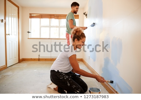 Stock photo: happy couple painting first home