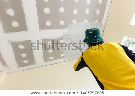 Stock photo: Decorator using a long roller to paint a ceiling