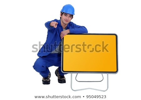 Stock photo: Man kneeling by road sign and pointing