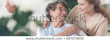 Foto stock: Nurse Talking To An Elderly Lady In A Wheelchair