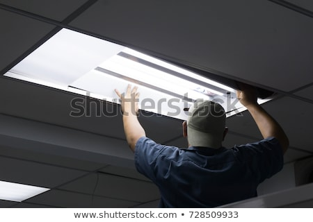 Stock photo: electrician replacing tube lighting