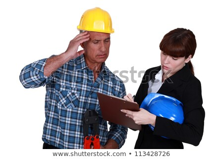 Confused tradesman watching an engineer writing on a clipboard Stock photo © photography33