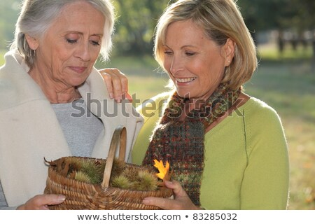 a mid age blonde woman and an older woman holding a wickerwork basket full of chestnuts Stock photo © photography33