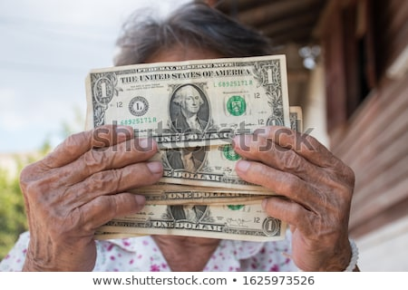 elderly woman holding money in hand stock photo © andersonrise