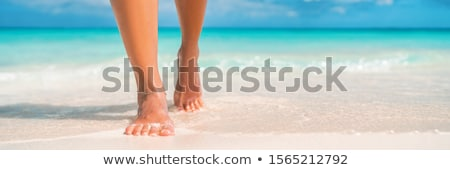 Woman comes into water on the beach Stock photo © Anna_Om