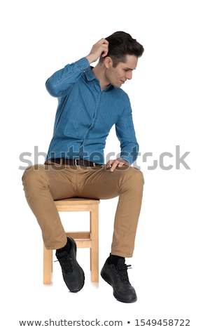 Moda człowiek posiedzenia patrząc w dół niebieski shirt Zdjęcia stock © feedough