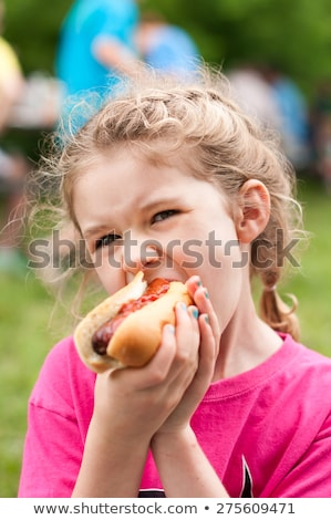 Kız yeme sosisli sandviç ışık köpek akşam yemeği Stok fotoğraf © ddvs71