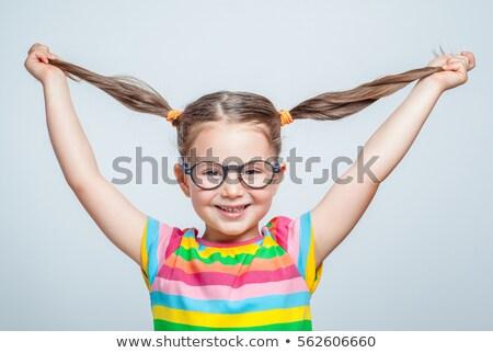 Closeup of playful beautiful girl playing with hair Stock photo © deandrobot