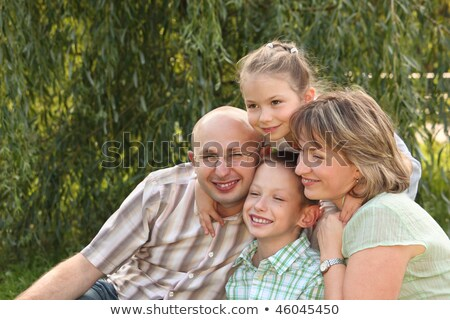 Cheerful family with two children in early fall park. father, mother, little boy and girl is sitting Stock photo © Paha_L