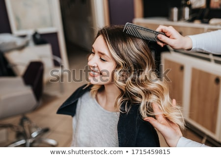 Woman hairdresser making hairstyle to young female Stock photo © deandrobot