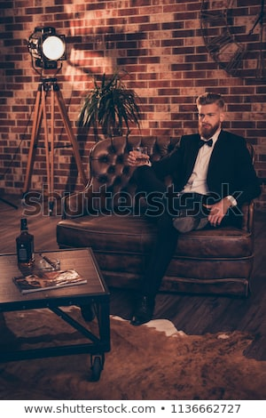 Serious handsome businessman drinking whiskey and smoking cigar sitting  Stock photo © deandrobot