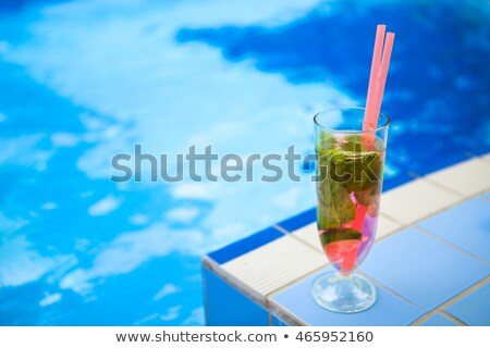 glass of refreshment drink with strawberry mojito on a pool side stock photo © yatsenko