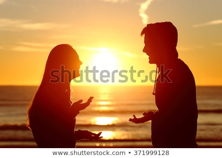 silhouette of couple standing face to face on beach at sunset stock photo © monkey_business