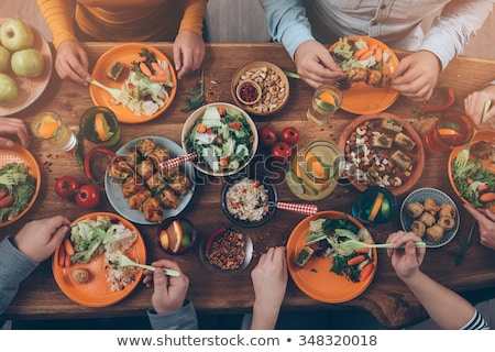Enjoying dinner with friends. Top view of group of people having Stock photo © Yatsenko