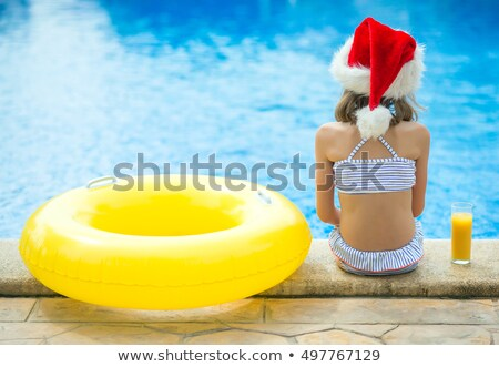 kid in swimsuit and santa hat with juice Stock photo © LightFieldStudios