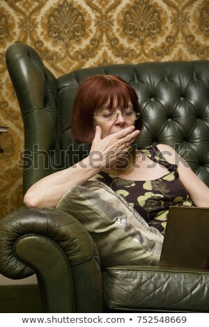 Mature Lady yawning whilst reading at ho Stock photo © IS2