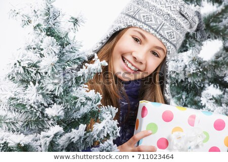 Girl holding a gift, beside snowy trees Stock photo © IS2